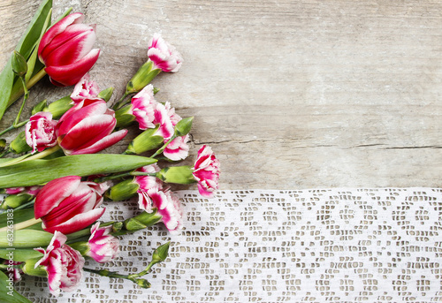 Beautiful pink tulips and carnations on wooden background