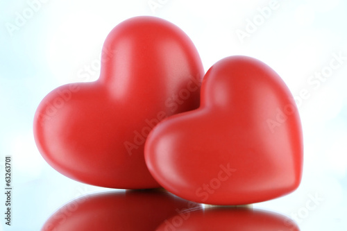 Red hearts on light background