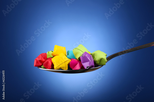 Paper stars in silver spoon on blue background