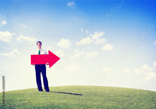 Business Man Outdoors Holding an Arrow Pointing Copy Space