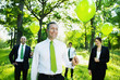 Eco-Friendly Business People Holding Green Balloons In The Woods