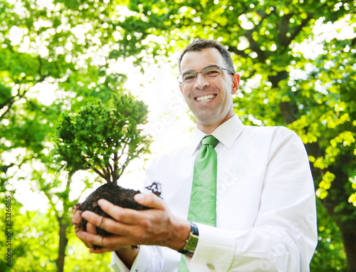 Businessman Holding A Tree To Plant In A Forest