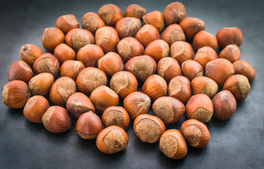 Hazelnuts on dark background. Selective focus.