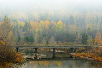 Bridge across mountain river in morning fog in autumn