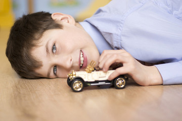 cheerful boy with a toy car.