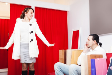 Man and woman choosing coat in fitting-room