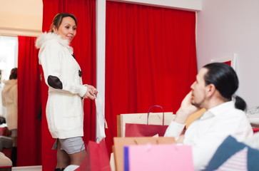 Woman trying coat in fitting-room