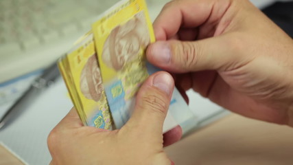 Hands Counting Ukrainian Hryvnia