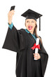 Female student holding diploma and taking selfie