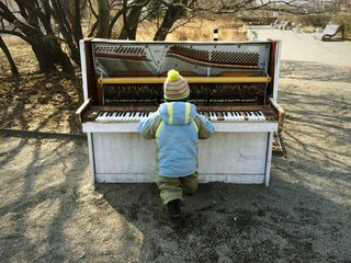 child playing on the piano in the park