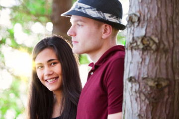 Young couple standing among trees, sunlight streaming