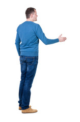 back view of man in movement reaches out to shake hands.