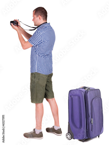 Back view of man photographing traveling with suitcase.