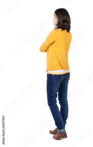 back view of standing young beautiful  brunette woman in yellow