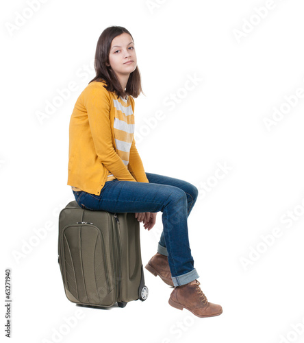side view of walking  woman  in cardigan sits on a suitcase.