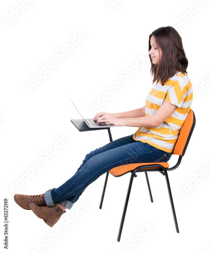 Side view of  woman sitting on a chair to study with a laptop.