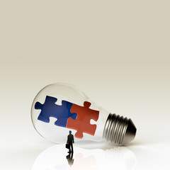 Light bulb and two puzzles with businessman as partnership conce