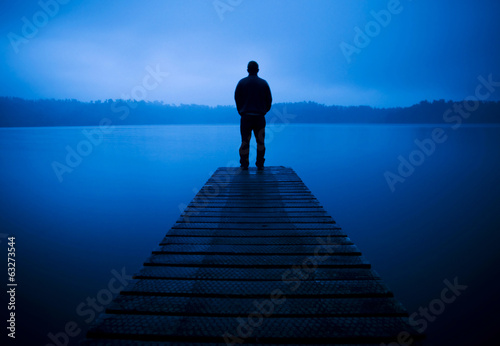 Man Standing on a Jetty by Tranquil Lake
