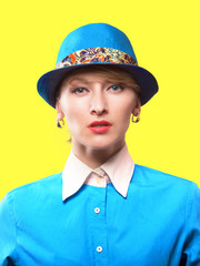 Woman in a hat looking at camera, yellow background