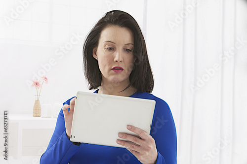 modern businesswoman  ,blue dress, holding tablet computer