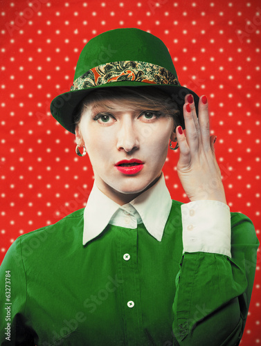 Old-fashioned woman in a green hat, red polka dot background