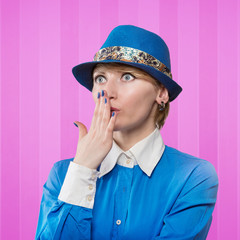 Woman in a blue hat covering the mouth with her hand