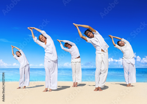 People performing yoga on the beach