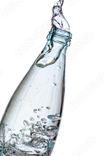 Glass bottle splashing water isolated on white