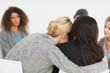 Women embracing in rehab group at therapy - 63274707
