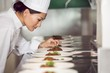 Concentrated female chef garnishing food in kitchen - 63274962