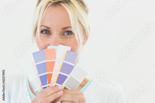 Closeup portrait of a beautiful woman holding color swatches