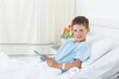 Boy using digital tablet in hospital bed
