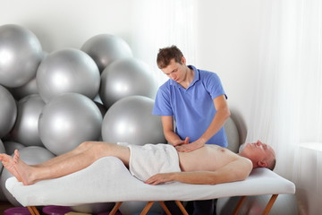therapist massaging middle age  man' s abdomen