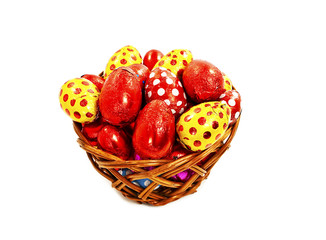 Colorful chocolate Easter eggs in basket on white background