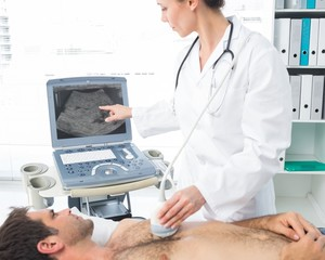 Cardiologist using sonogram on male patient