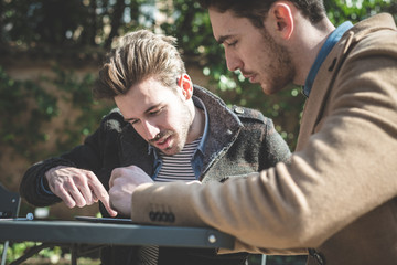 two young handsome fashion model businessmen using tablet