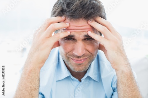Attractive man sitting on the couch with headache looking at cam