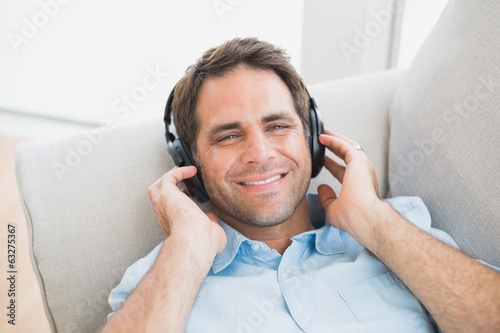 Smiling handsome man lying on sofa listening to music looking at