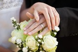 Newlywed couple with wedding rings and bouquet