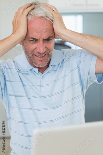 Stressed man using his laptop