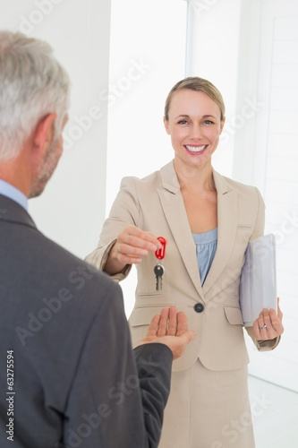 Smiling estate agent giving house key to happy customer