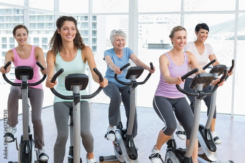 Happy women working out at spinning class