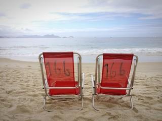 Red empty chairs in Copacabana beach, Rio de Janeiro