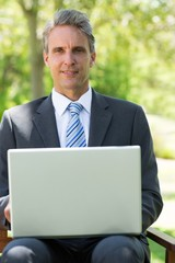 Confident businessman with laptop at park