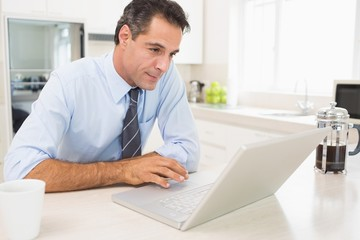Concentrated well dressed man using laptop in kitchen