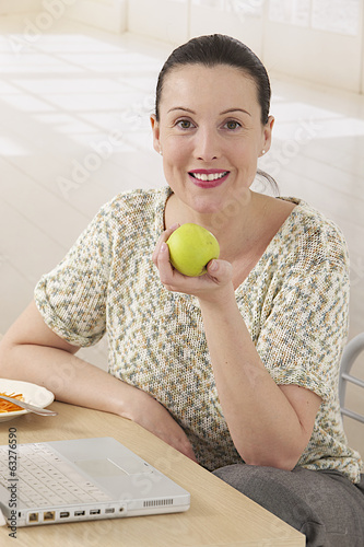 Portrait of a  business woman leating a green apple