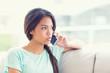 Pretty girl sitting on sofa making a phone call