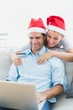 Cute couple in santa hats shopping online with laptop