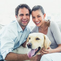 Happy couple petting their yellow labrador on the couch