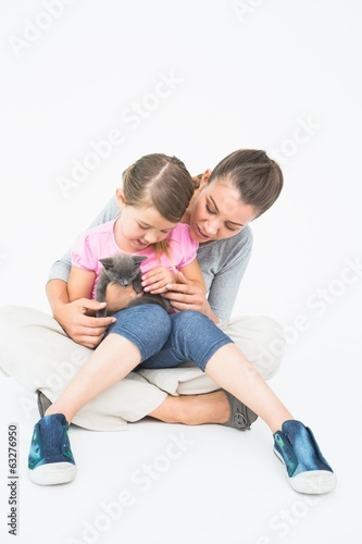 Cute daughter and mother sitting with pet kitten together